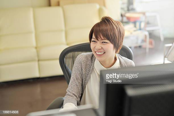 businesswoman sitting in office,smiling - 首をかしげる ストックフォトと画像