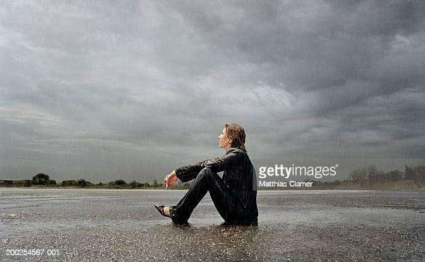 businesswoman sitting in rain, side view - mouillé photos et images de collection