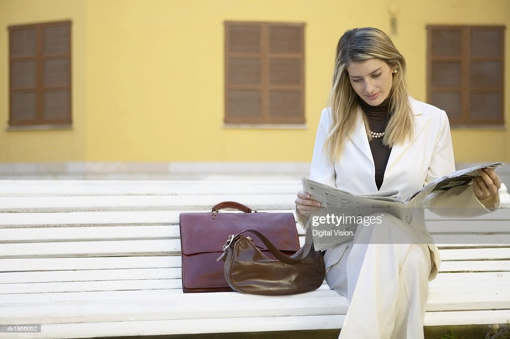 Businesswoman Sitting on a Bench in the City and Reading a Newspaper : Stock Photo