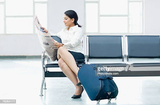 Businesswoman sitting on a chair at an airport and reading a newspaper