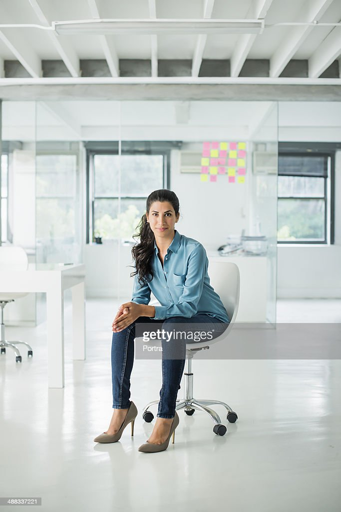 Businesswoman sitting on a chair in open office : Stock Photo