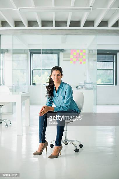 businesswoman sitting on a chair in open office - sitting fotografías e imágenes de stock