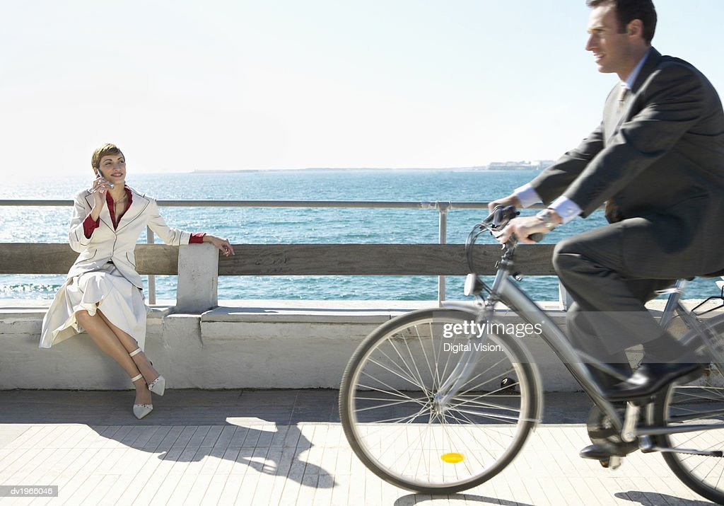 Businesswoman Sitting on a Concrete Bench by the Waterfront as a Businessman Rides Past on a Bicycle : Stock Photo