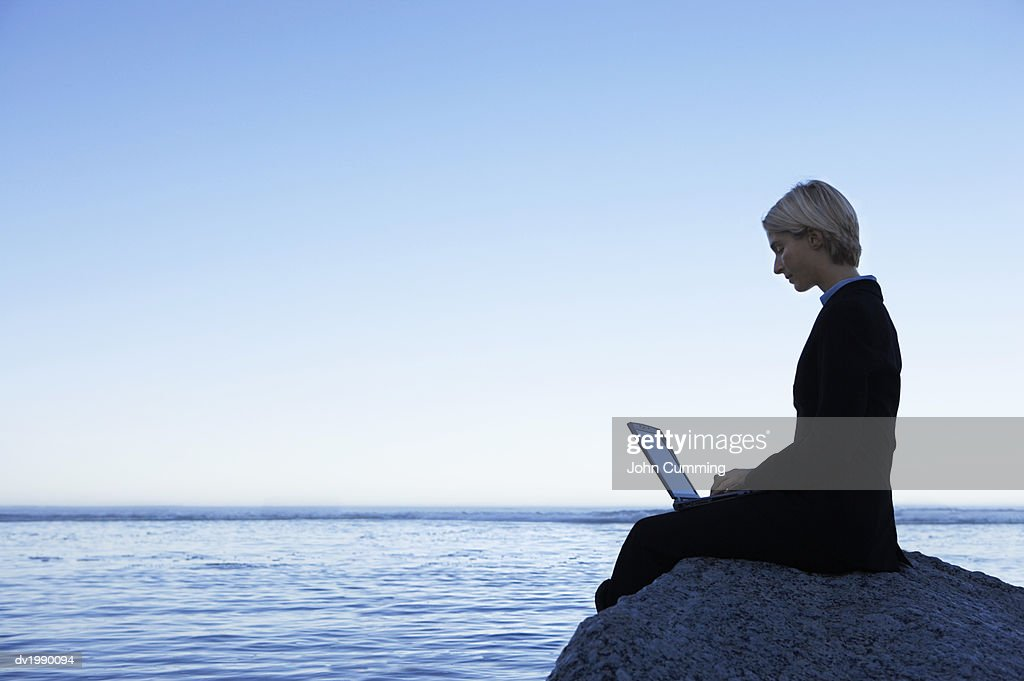Businesswoman Sitting on a Rock in the Sea and Using a Laptop Computer : Stock Photo