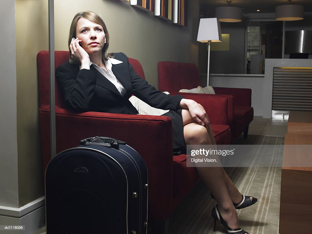 Businesswoman Sitting on a Sofa by Her Briefcase and Using a Mobile Phone : Stock Photo