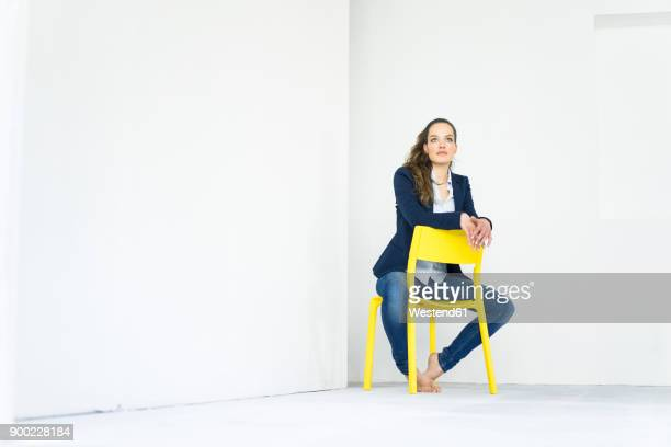 businesswoman sitting on a yellow chair thinking - yellow blazer stock photos and pictures