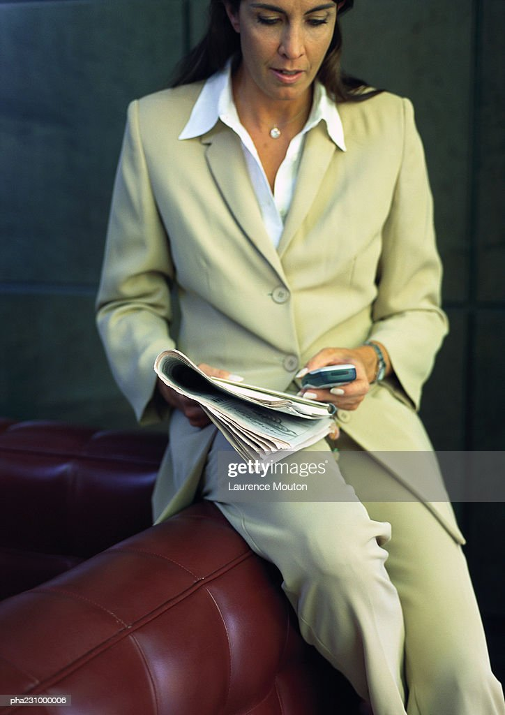 Businesswoman sitting on back of a sofa with a newspaper and cell phone, portrait : Stockfoto