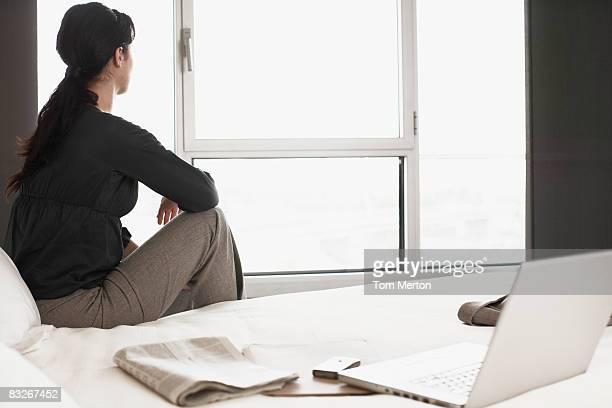 Geschäftsfrau sitzt auf dem Bett im Hotelzimmer