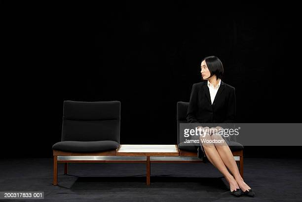Businesswoman sitting on bench looking to one side