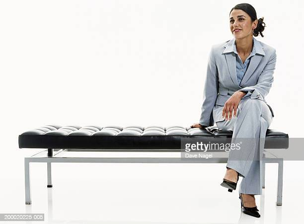 businesswoman sitting on bench - sitting foto e immagini stock