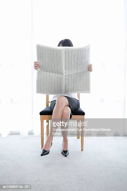 Businesswoman sitting on chair, reading newspaper, front view