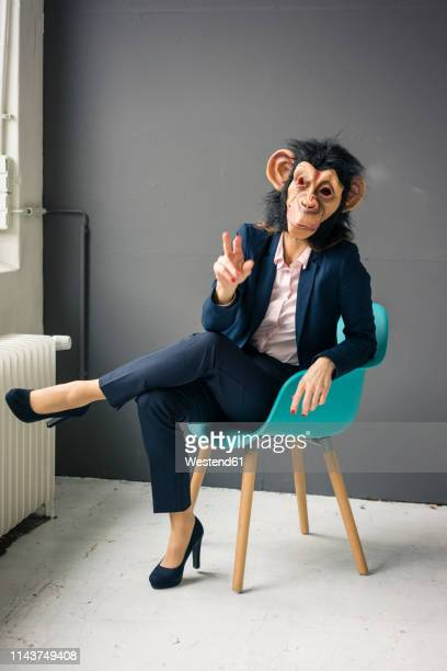 businesswoman sitting on chair, wearing monkey mask, gesturing - monkey suit stock pictures, royalty-free photos & images