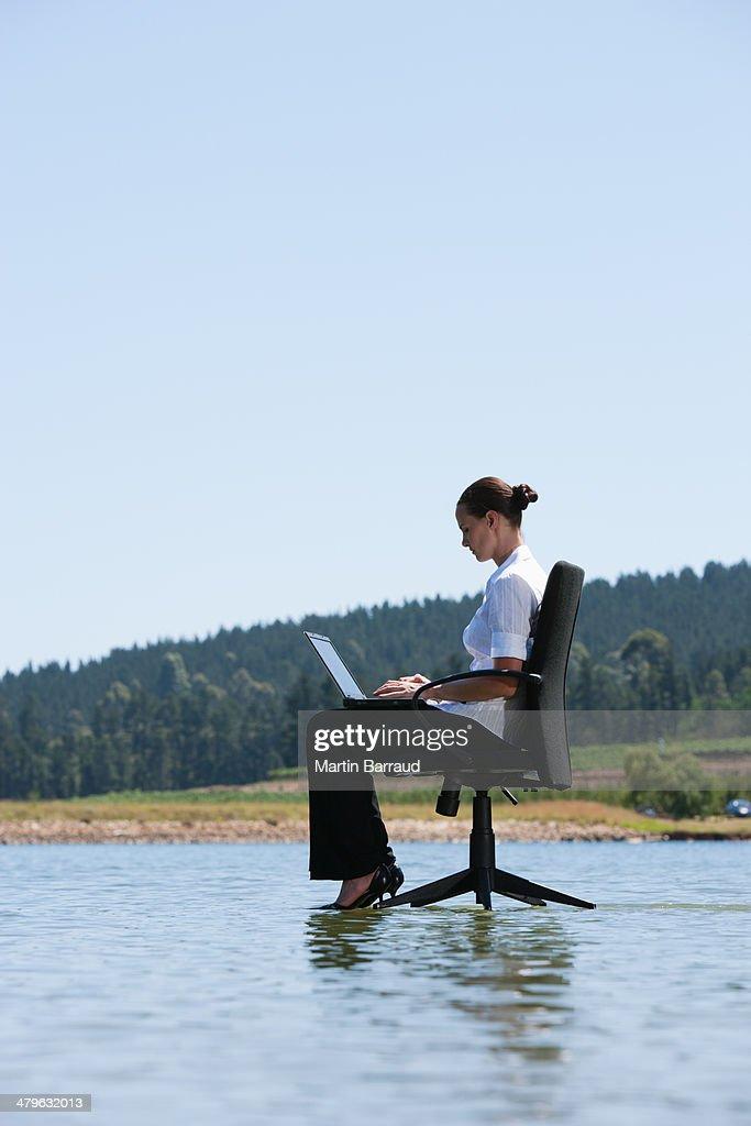 gesch ftsfrau sitzend auf stuhl mit laptop im wasser stock foto getty images. Black Bedroom Furniture Sets. Home Design Ideas