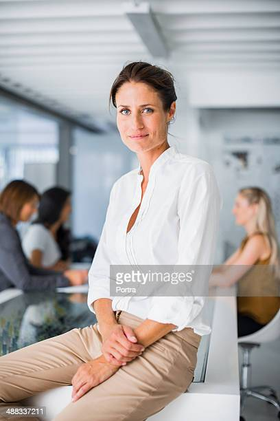 businesswoman sitting on conference table - blouse stockfoto's en -beelden