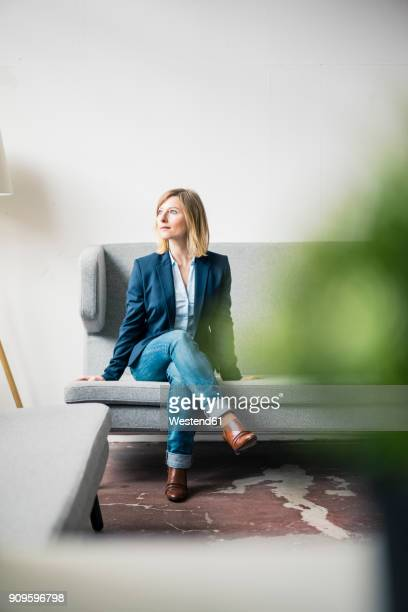 Businesswoman sitting on couch in office lounge