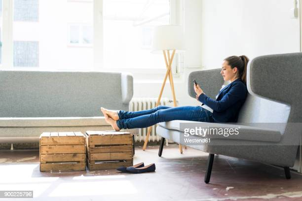 Businesswoman sitting on couch using cell phone