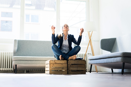 Businesswoman sitting on crate practising yoga - gettyimageskorea