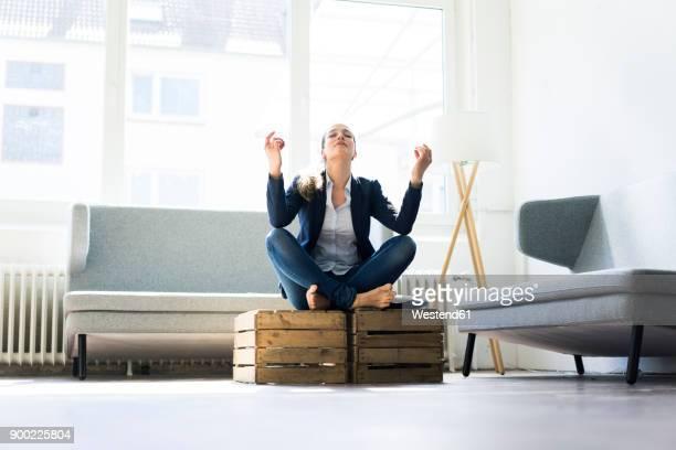 Businesswoman sitting on crate practising yoga