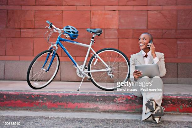 Businesswoman sitting on curb using digital tablet and cell phone