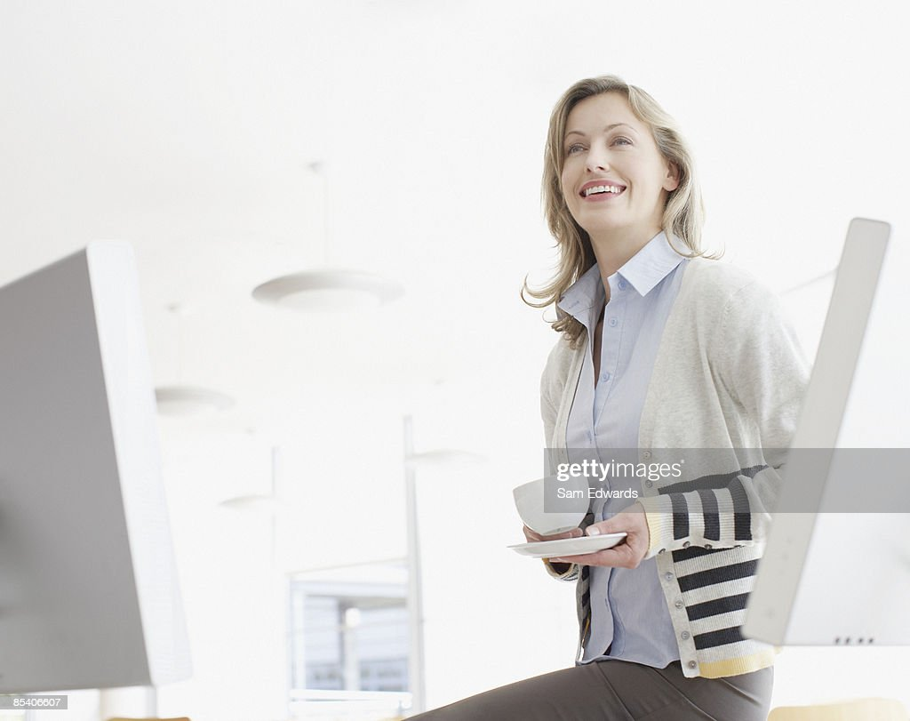 Businesswoman sitting on desk drinking coffee : Stock Photo