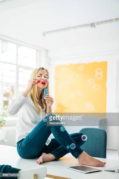 businesswoman sitting on desk in office blowing soap bubbles - donne bionde scalze foto e immagini stock