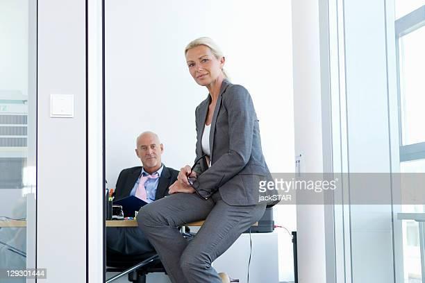 Businesswoman sitting on desk in office