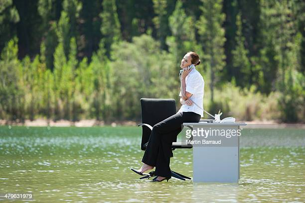 Businesswoman sitting on desk in water with phone