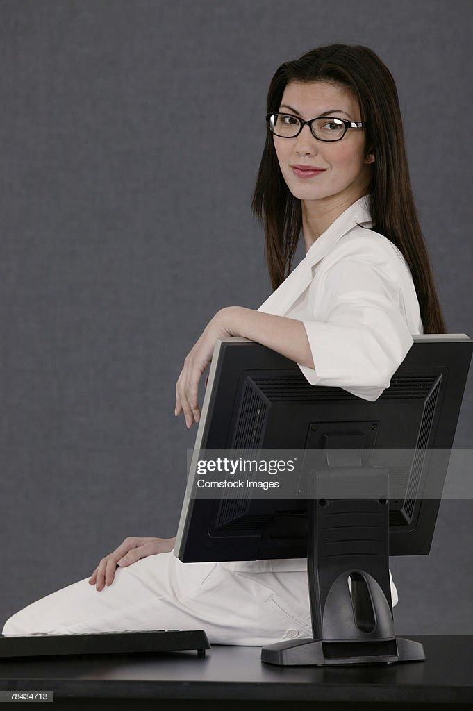 Businesswoman sitting on desk : Stockfoto