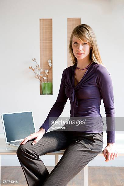 businesswoman sitting on desk, portrait - hand on knee stock pictures, royalty-free photos & images