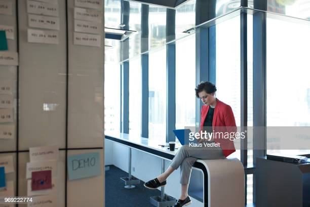 businesswoman sitting on desk & typing on laptop - non binary gender stock pictures, royalty-free photos & images