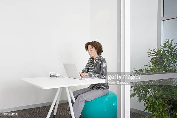 businesswoman sitting on exercise ball in office - ergonomics stock photos and pictures