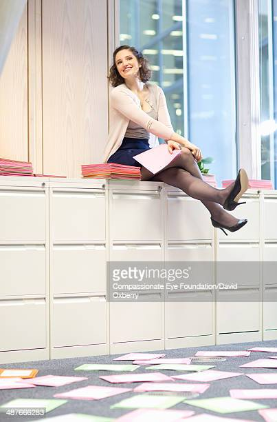 Businesswoman sitting on filing cabinets in office