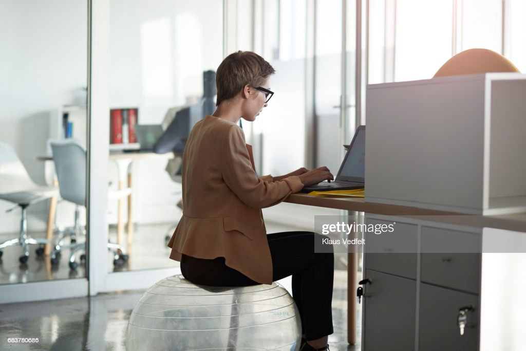 Businesswoman sitting on fitness ball, at office desk : Stock Photo