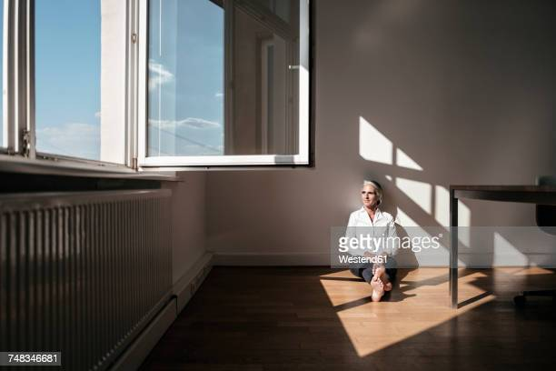 Businesswoman sitting on floor in office