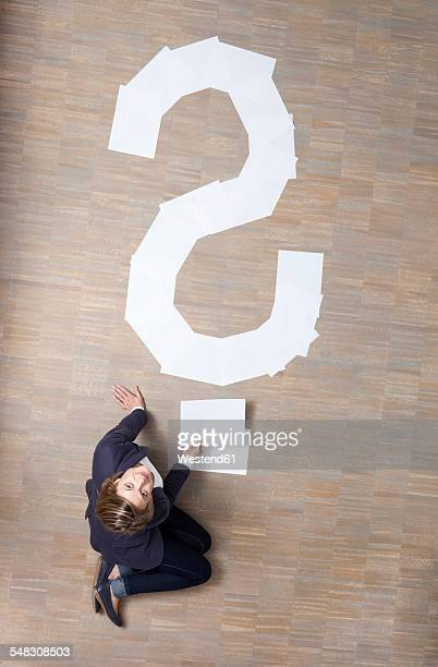 Businesswoman sitting on floor with blank sheets of paper in shape of question mark