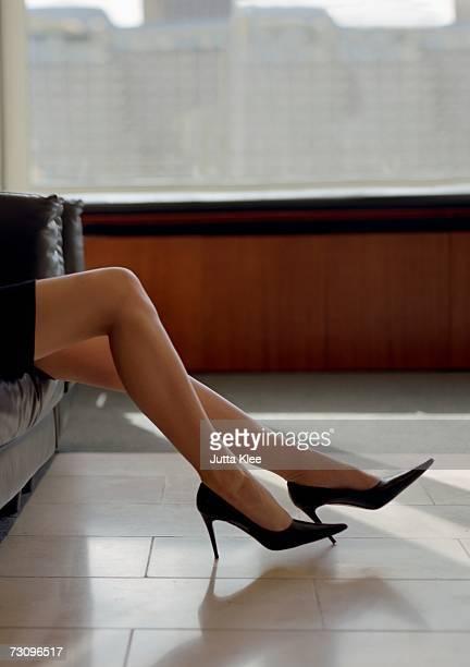 businesswoman sitting on leather sofa, low section - beautiful legs in high heels stock-fotos und bilder