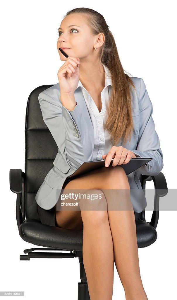 Empresaria sentado en silla de oficina con portapapeles y lápiz : Foto de stock