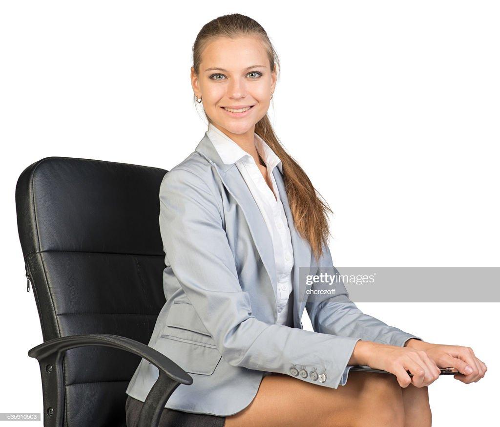 Geschäftsfrau sitzt auf Stuhl mit Zwischenablage im Büro : Stock-Foto