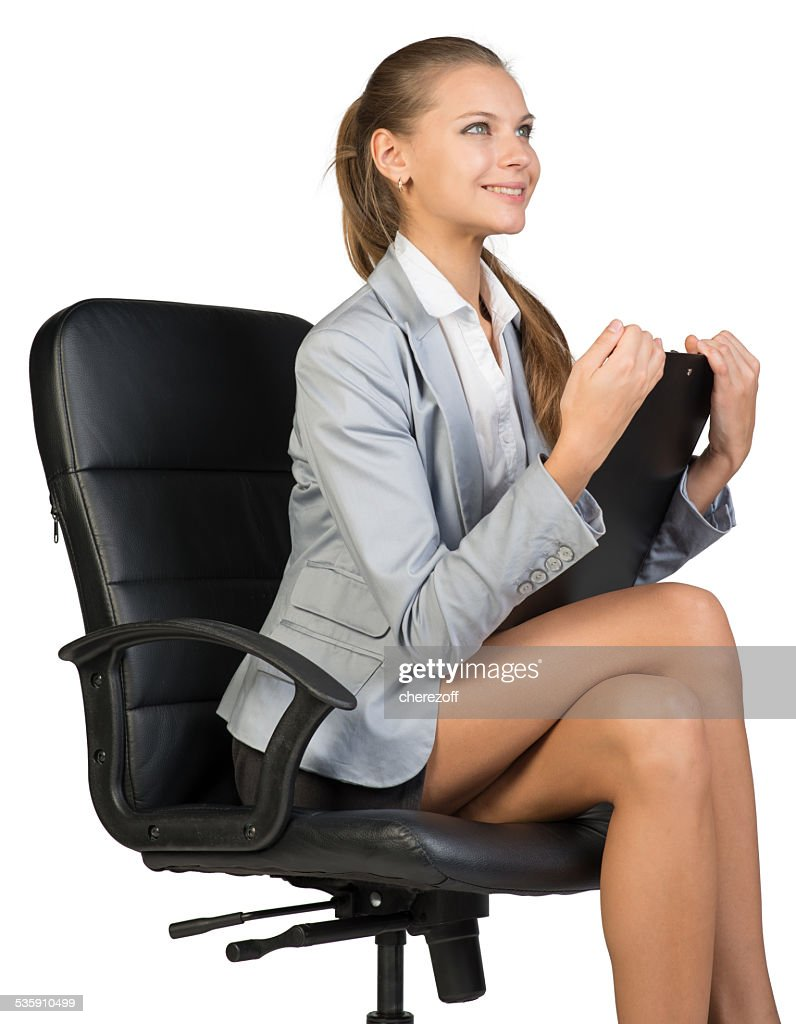 Businesswoman sitting on office chair with clipbord in hands, looking : Stock Photo