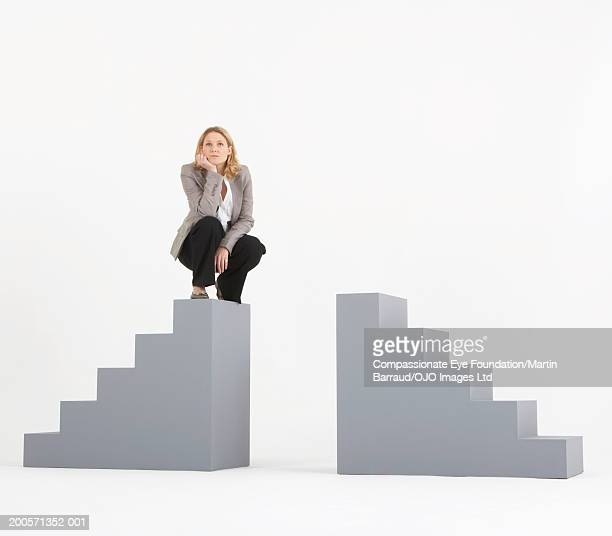 Businesswoman sitting on one of two staircase shaped objects