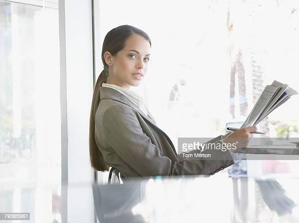 Geschäftsfrau sitzt auf dem Außenpatio mit Zeitung