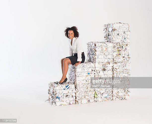 Businesswoman sitting on stack of paper bales