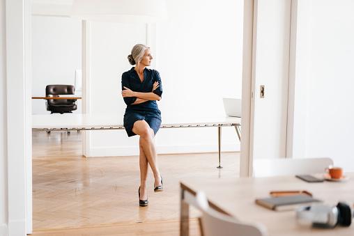 Businesswoman sitting on table in modern office - gettyimageskorea