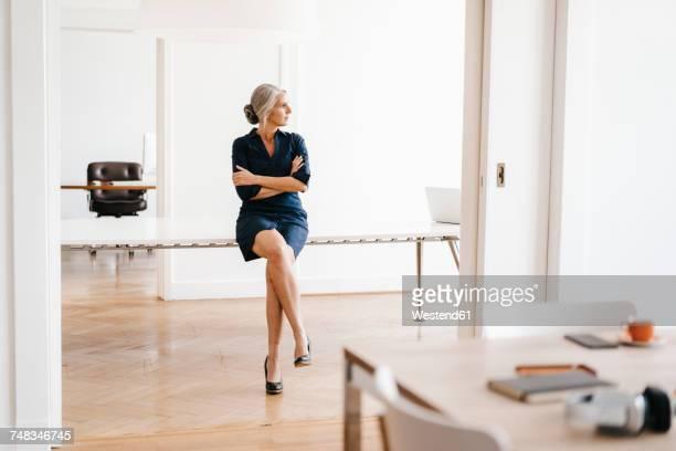 businesswoman sitting on table in modern office - businesswear fotografías e imágenes de stock