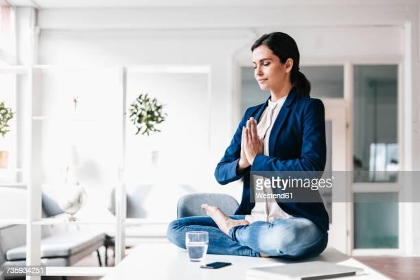 Businesswoman sitting on table meditating