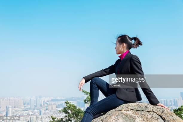 Geschäftsfrau, die sitzen oben auf dem Berg