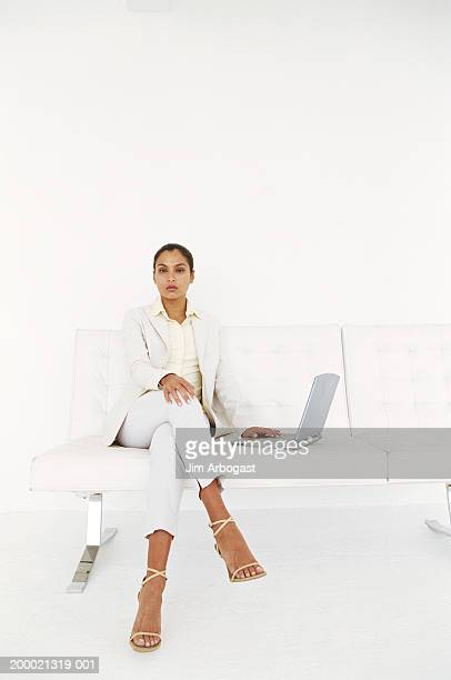 Businesswoman sitting on white sofa with laptop computer