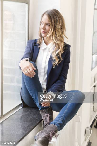 Businesswoman sitting on window sill of her office