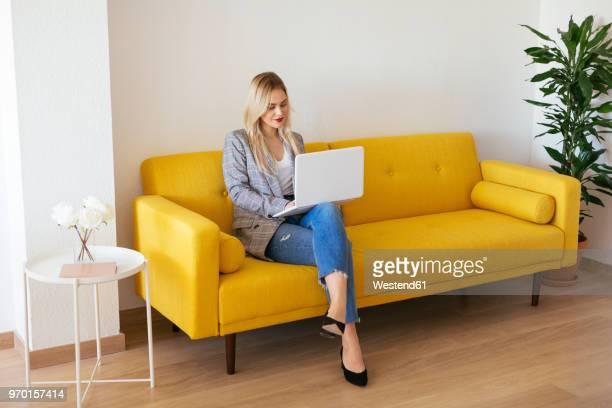 businesswoman sitting on yellow couch, using laptop - 若い女性だけ ストックフォトと画像