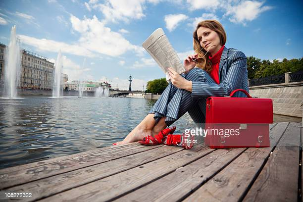 Businesswoman sitting outdoors and reading newspaper